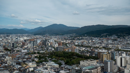 Aerial shots of the city of Kyoto. Skyscrapers and buildings expand out into the distance of the Japanese city as a stormy sky and clouds form over the cityscape.