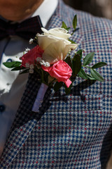 Elements of the groom's clothes on the wedding day. Blue butterfly, tuxedo and boutonniere with white roses