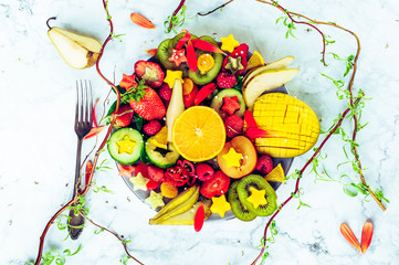 Colourful fresh fruit platter with strawberries, mango, kiwis and pears