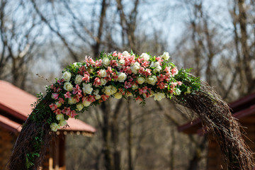 round wedding arch from branches decorated with flowers and decor around it
