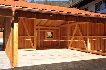 Neuer Carport aus lasiertem Holz mit Kupfer-Dachrinne und Regenfallrohr, alpine Architektur