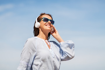 music, people and technology concept - happy smiling woman with headphones over blue sky