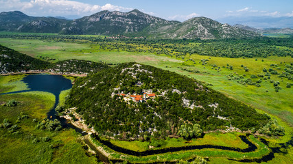 Aerial view of the landscape of Lake Skadar in the mountain and the island with monastery on a beautiful sunny day. Montenegro. The territory of Lake Skadar overgrown with plants.