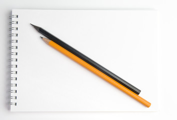 The pencil lying on the notebook. Close up.