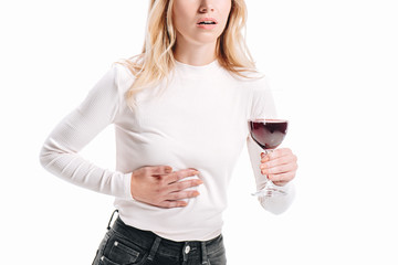 cropped image of woman showing liver pain and holding glass of red wine isolated on white