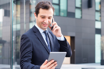 Modern manager using mobile phone and digital tablet