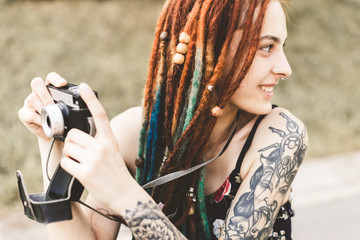 young girl with tattoos and dreadlocks photographs vintage camera in the park