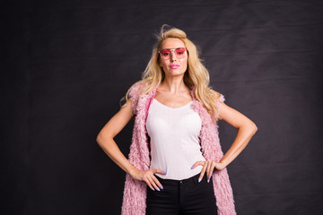 Fashion and beauty concept - Close up portrait of blond model dressed in white shirt and pink cardigan over dark background.