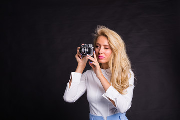 Photographing, fashion and people concept - young blonde woman making a photo from something on black background with copy space