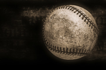 an old and used vintage baseball on a dark wooden background