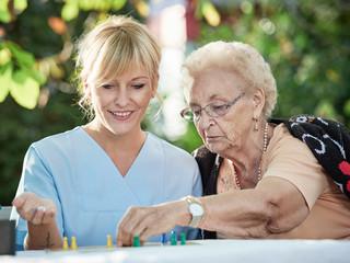 Pflegerin spielt mit Seniorin ein Brettspiel