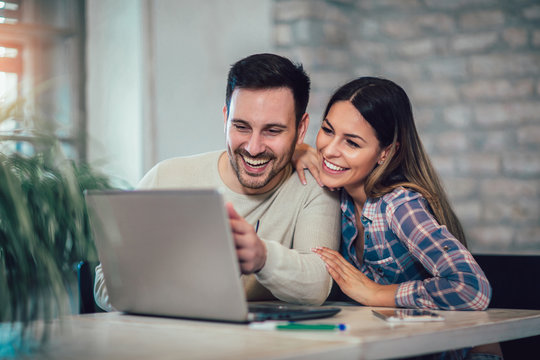 Young Couple Using Laptop On Desk At Home