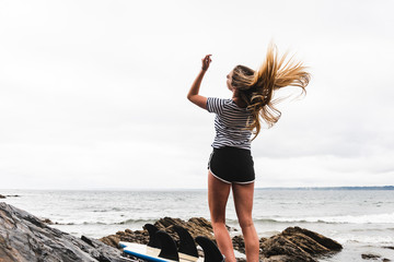 Young woman with surfboard dancing on the beach