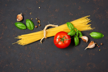 Spaghetti with tomatoes garlic and basil isolated on black background. Top view.
