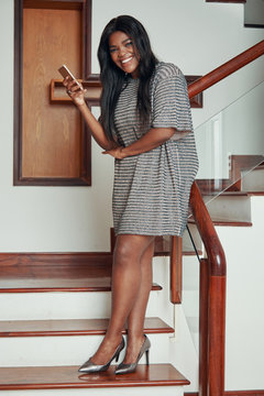 Side view of cheerful trendy black woman in dress and heels standing on wooden stairs of house with phone smiling at camera