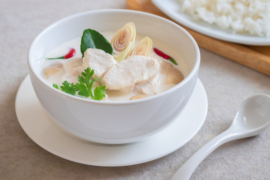 Chicken with coconut milk soup in bowl and rice on plate , Thai food (Tom Kha Kai).
