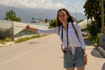 A woman on the side of the road catches a passing car, hitchhiking