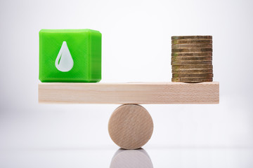 Cubic Block With Waterdrop Icon And Coins Balancing On Seesaw