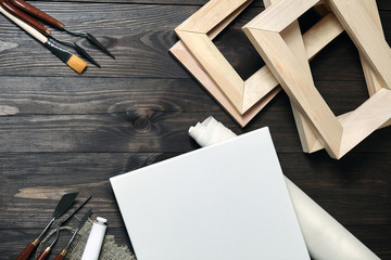 A white blank canvas, palette knives, synthetic paintbrush, a tube with oil or acrylic paint and stretchers lying on a brown wooden background. Top view