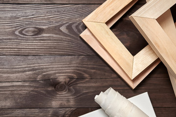Wooden stretchers and a rolled canvas lying on a dark wooden background with copy space. Wood products: Subframes. Top view