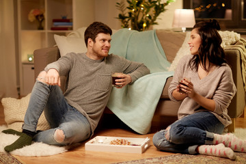 hygge, leisure and people concept - happy couple drinking coffee and eating at home