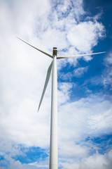 The image behind the wind turbine for electricity on a cloudy day in the blue sky.