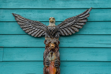 totem pole with bear and eagle in front of a turquoise background