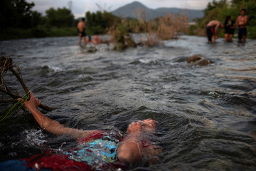 Migrant girl from Honduras baths in fresh water stream as caravan of thousands from Central America en route to the United States take rest in Pijijiapan