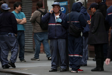 Postal workers stand on the street during a report of a suspicious package in the Manhattan borough of New York