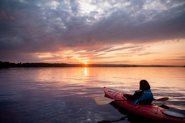 Woman in a kayak on the river on the scenic sunset