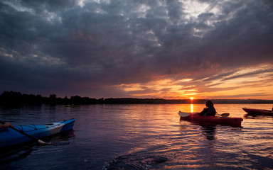 People in kayaks on the river on the scenic sunset