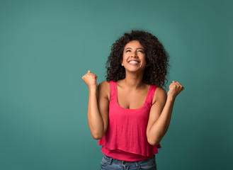 Happy woman celebrating her success on blue background