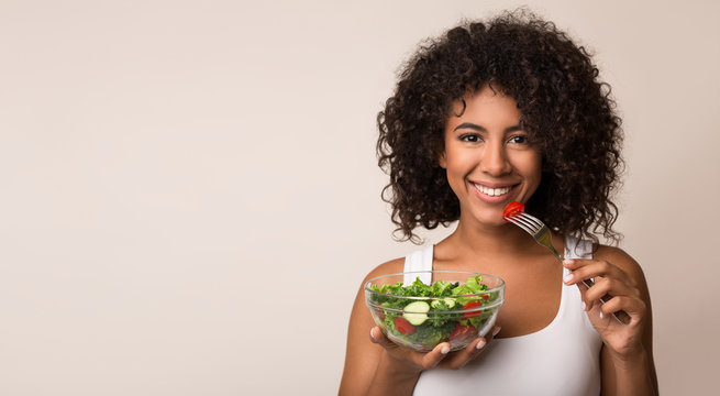 African-american woman eating vegetable salad over light background