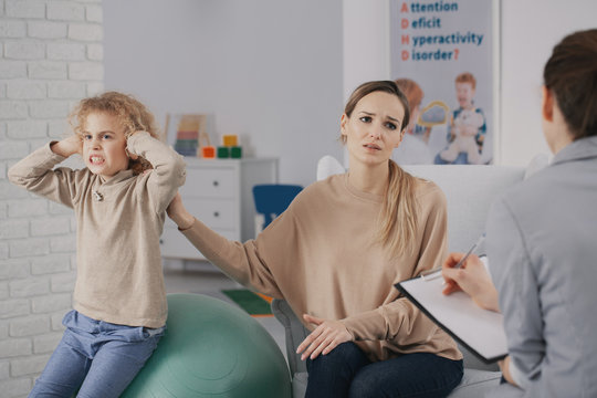 Sad woman and rebellious child with adhd during therapy with psychotherapist