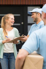 Smiling couriers giving packages to happy customer signing receipt