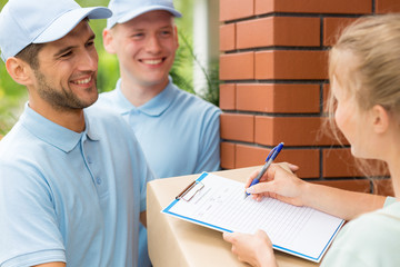 Smiling friendly couriers in blue uniforms and woman signing receipt of package delivery