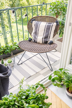 Top view of stylish rattan chair with patterned pillow on the balcony of modern flat, real photo