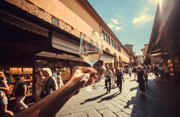 Wine glass in hand of tourist over crowd between old buildings of Florence, Tuscany. Ancient city in Italy. UNESCO World Heritage Site