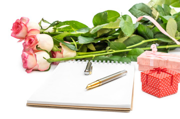 Bunch of roses with blank notepad and gift boxes on white.