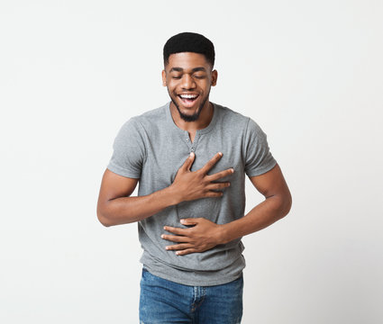 Young african-american man laughing out loud in studio
