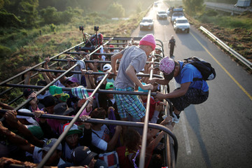 Migrants, part of a caravan of thousands from Central America en route to the United States, hitchhike on a truck along the highway to Arriaga from Pijijiapan
