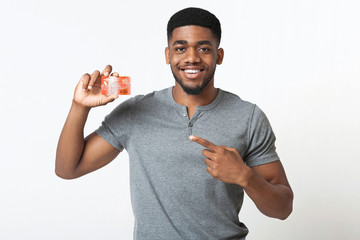 Cheerful african-american man pointing at credit card