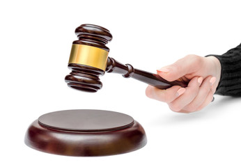 Female's hand holding judge's gavel over stand. Law concept.