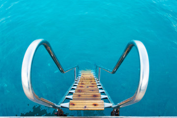 Ladder leading into the refreshing crystal water of a sea. Wooden steps to turquoise ocean water
