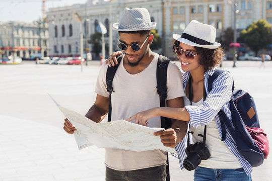 Loving couple planning walk route with map