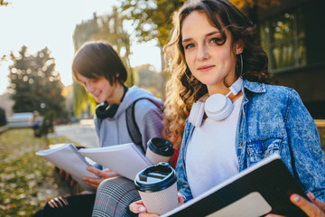Two male and female hipster students studying reading notes drinking coffee together outdoors sitting on the bench.