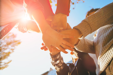 A group of four friends students man and women handshake high five teamwork concept of tenagers friendship, sunny autumn mood . Bottom view