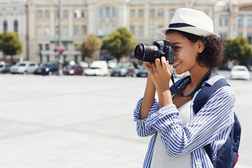 African-american woman photographing with camera on vacation