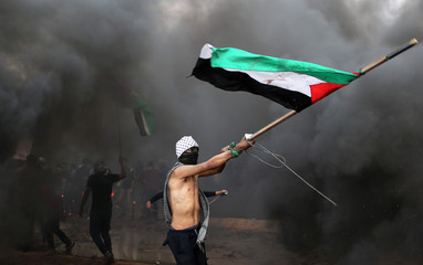 Demonstrator waves a Palestinian flag during a protest at the Israel-Gaza border fence in Gaza