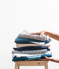 Woman hands take stack of blue and beige laundry